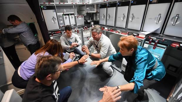 Lockerungsübungen mit Testpassagieren in der Bordküche des Fluges QF7879