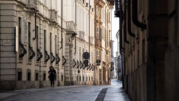 Eine Frau läfut durch die leeren Straßen im norditalienischen Asti
