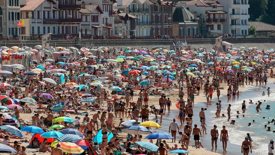 Menschen genießen das sommerliche Wetter am Strand. In Frankreich wird eine zweite Welle der Covid-19-Pandemie befürchtet.